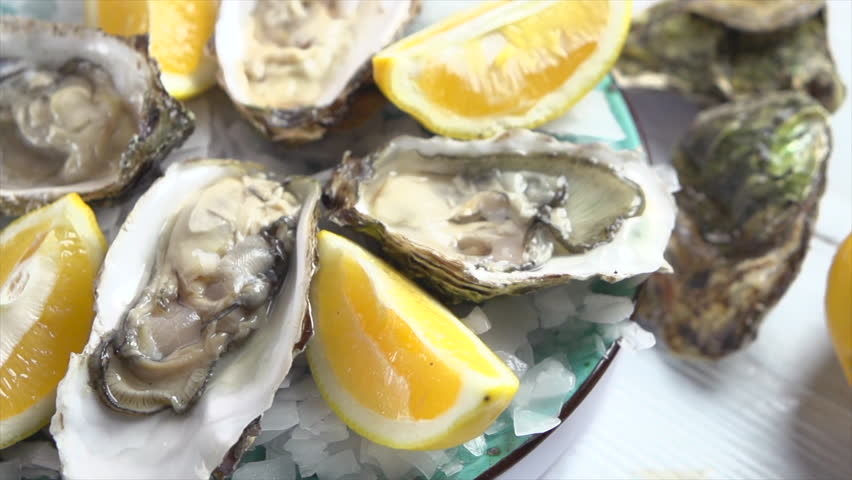 Oysters on ice with lemon closeup. Fresh Oyster on half shell on big plate in restaurant. Served table. 4K UHD video slow motion