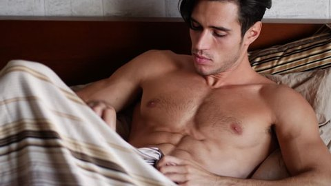 Handsome shirtless muscular young man in bed typing on cell phone, sending text message or dialing number or reading web pages