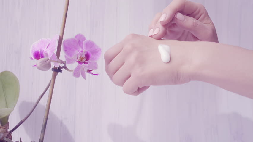 Closeup shot of tender woman hands apply skin cream. light background with violet orchid. Beautiful hands with elegant manicure. Shallow depth of field, soft focus on hands. Skincare concept. 4k UHD.