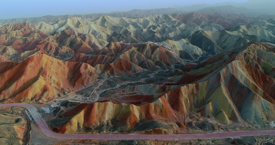 Flying through most spectacular section of Zhangye Danxia National Geopark showing colorful rainbow mountains covered with unique patterns.