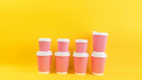 Pink and yellow coffee cups. Video footage timelapse stop motion. Funny changing size movie. Bright cheerful yellow background.