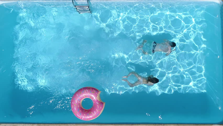 Aerial - Couple diving in the pool at the same time. A fun summer day in the pool at home