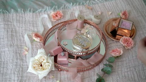 Woman put flowers at pink tray with bridal earrings proposal ring and perfume steadicam