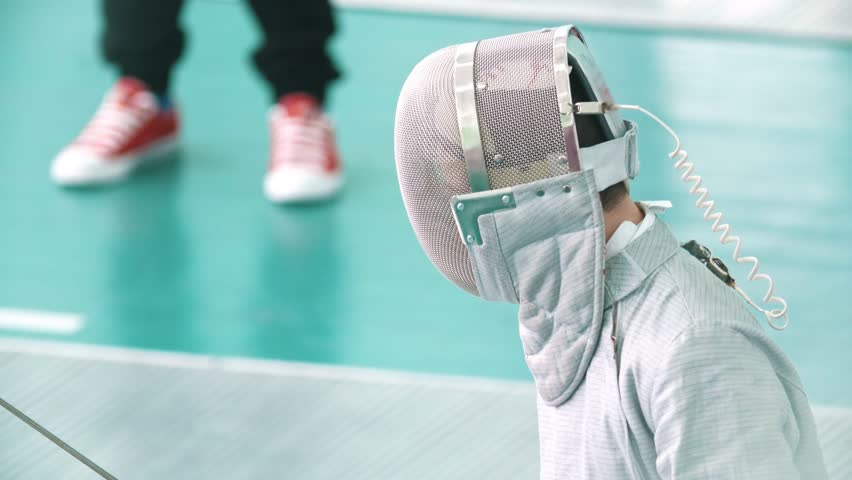 Young boy with rapier in protective mask in a fencing tournament | Shutterstock HD Video #1009034447