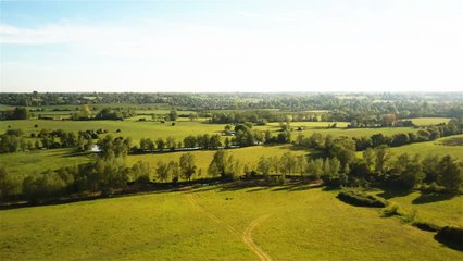 English countryside, Suffolk. Aerial drone video footage rising to reveal the patchwork expanse of rural fields and farmland in the heart of the flat Suffolk countryside in the south-east of England.