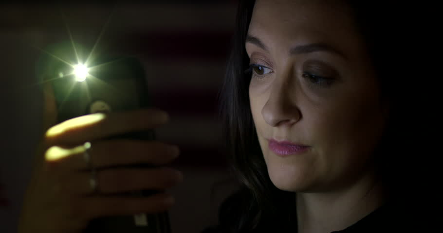 BCU young woman using cellphone at night, turns from screen with serious look on her face. Hand-held 4K with lens flares. Stripes of flag faintly visible behind.