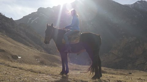 Young beautiful girl riding a horse in back lighting in the mountains