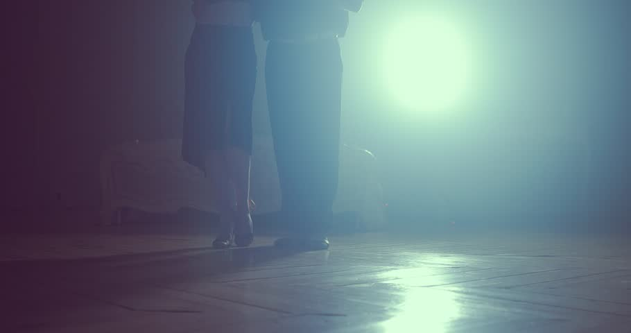 Final point in dances performed by two ballroom dancers. Silhouette in smoky studio
