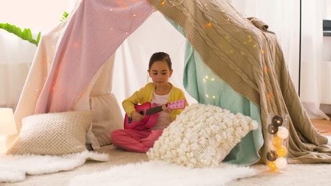childhood and hygge concept - happy little girl with toy guitar playing music in kids tent at home