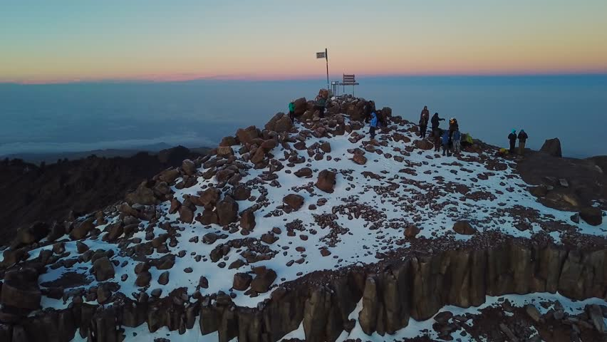aerial view of unrecognizible climbers on summit of the Lenana peak of Mount Kenya during sunrise