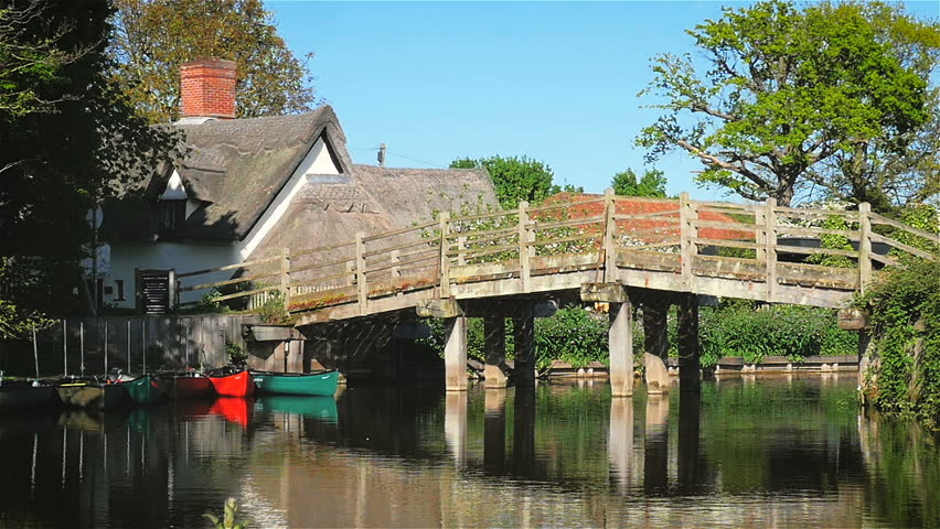 Flatford Bridge over the River Stour, Suffolk, England. A quaint typically English rural countryside scene with an old footbridge crossing the River Stour into the small village of Flatford, Suffolk.