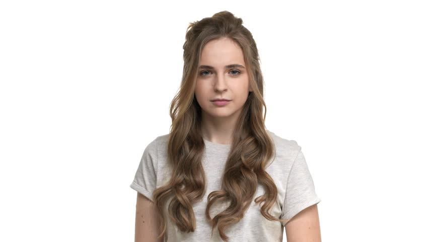 Studio portrait of hesitating woman in casual t-shirt thinking or counting pros and cons, isolated over white background closeup. Concept of emotions