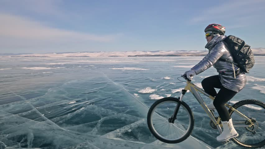 Woman is riding bicycle on the ice. The girl is dressed in a silvery down jacket, cycling backpack and helmet. Ice of the frozen Lake Baikal. The tires on the bicycle are covered with special spikes