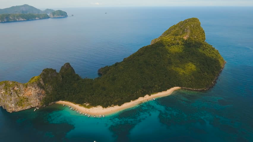 Beautiful beach with boats and tourists. Tropical bay in El Nido. Aerial view: bay and the tropical island. Aerial video. Tropical lagoon with turquoise water and white sand. Seascape: mountains