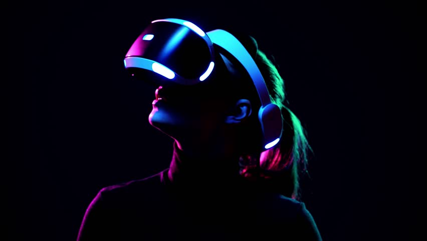 Young woman in VR headset looks around and wonders how amazing. Virtual reality helmet on black background | Shutterstock HD Video #1009215587