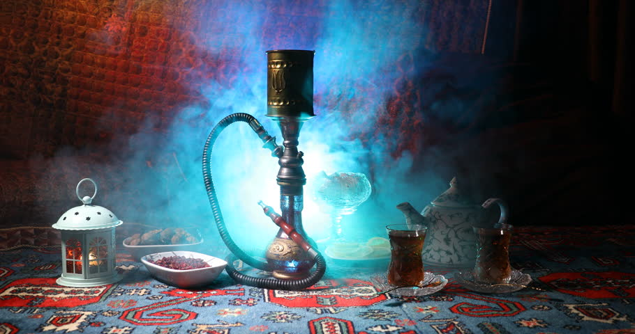 Hookah hot coals on shisha bowl making clouds of steam at Arabian interior. Oriental ornament on the carpet eastern tea ceremony. Stylish oriental shisha in dark with backlight. Slider shot