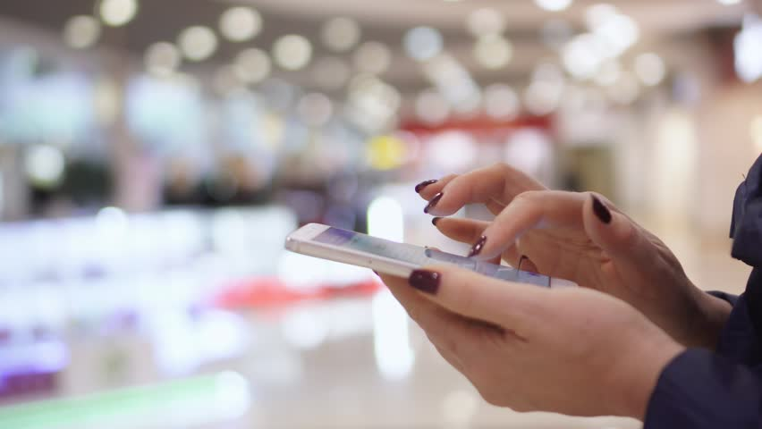Close-up view of female hands holding smartphone, using the touchscreen technology. Woman spending time in shopping mall. hands close up. The woman in trade mall. The woman in trade mall. The woman