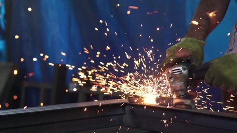 Worker grinding metal, metal grinding machine with sparks, metal sawing. Super slow motion 200 fps