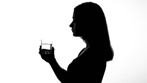 Female silhouette drinking glass of water, restoring ph balance, weight loss