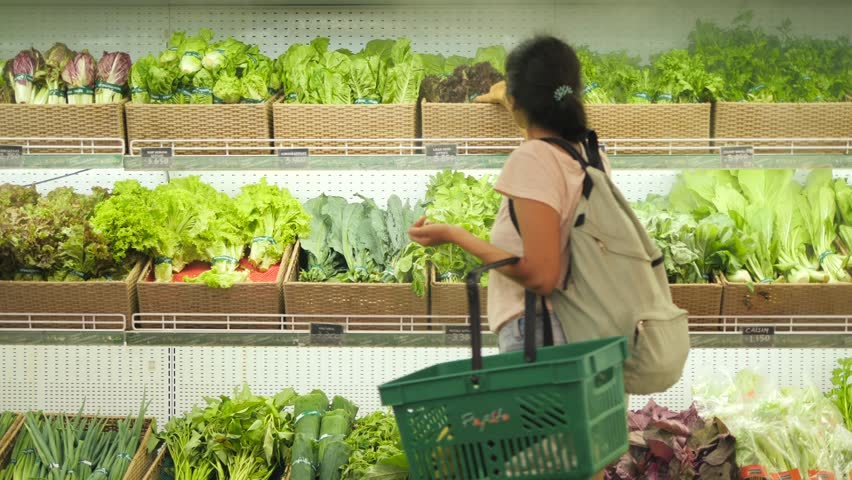 Young Mixed Race Woman Shopping in Grocery Store. Vegan Girl Choosing Fresh Green Salads and Organic Veggies. 4K.