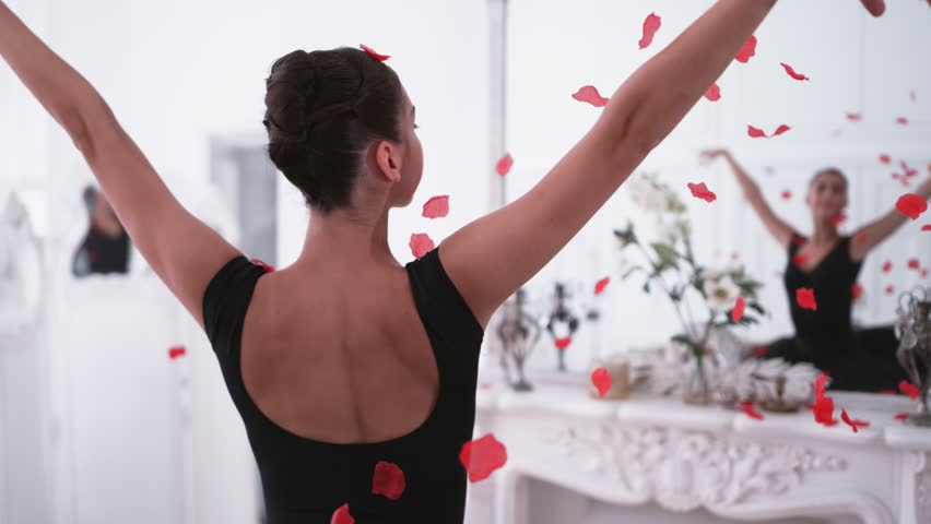 Graceful ballerina throwing red petals in slow motion