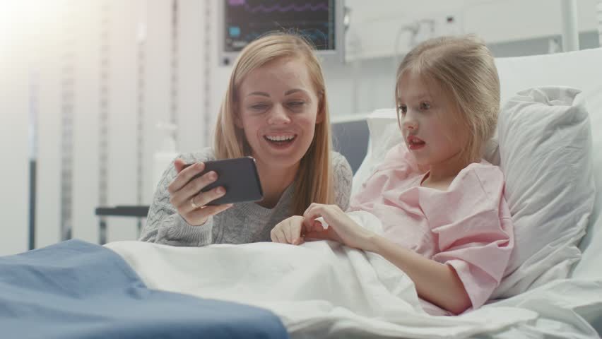 Cute Little Girl Lies on a Bed in the Children's Hospital, Her Mother Sits Beside, They Watch Cartoons/ Funny Videos on Smartphone. Modern Pediatric Ward.