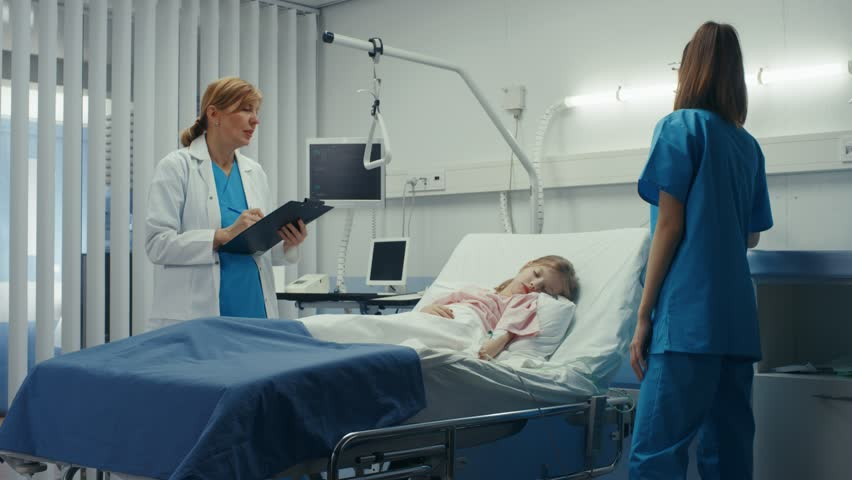 Sick Little Girl Lies on a Bed In the Hospital, Friendly Doctor Writes Medical Record/ Data into Clipboard, Talks with Nurse. Shot on RED EPIC-W 8K Helium Cinema Camera. #1009293617