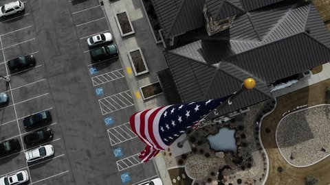 Aerial view above the American Flag waving on a flag pole.