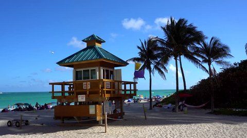 Lifeguard tower on a bright sunny summer day, with blue sky, palm trees and Atlantic Ocean in the background. Helicopters flying in the sky. World famous travel location. Miami beach, Florida.