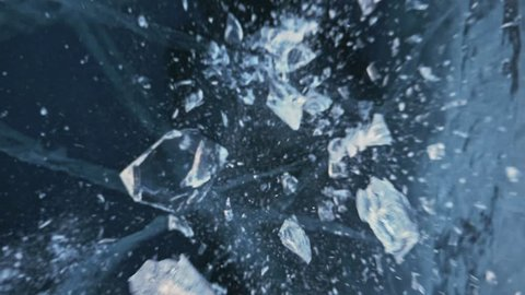 Man in the mittens smashes the ice on the ice. Slow motion. The camera moves behind the ice. A piece of ice is very beautifully broken about the icy with magical cracks. In the frame, a lot of