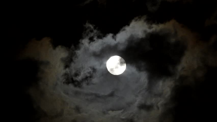 Full moon on a dark night with clouds moving over it