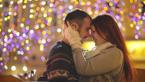 Romantic Couple with the Caucasian Appearance Kissing and Cuddling. Lights and Fireworks are On Background. Young Couple Canoodling with Yourself This Romantic Night.