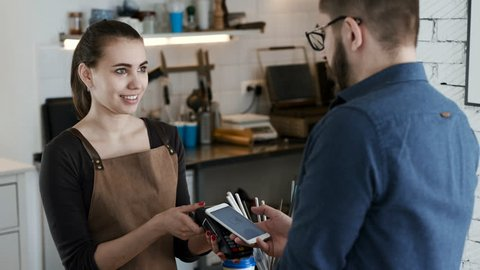 Attractive female employee near cash desk of restaurant store with creative interior for breakfast or lunch. Nfc cellhone of male buyer with cashless wallet of e-money for pos card reader and checkout