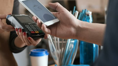 Female employee near cash desk of restaurant store for breakfast or lunch. Nfc cellhone of male buyer with cashless wallet of e-money for pos card reader and checkout. Morning life of modern people