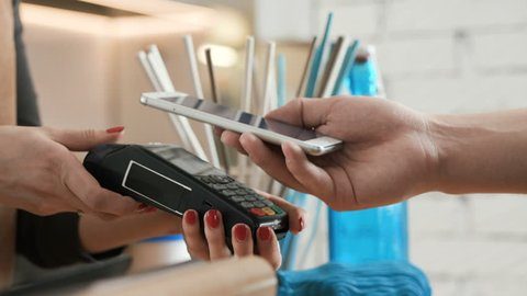 Female employee near cash desk of restaurant store for breakfast or lunch. Nfc cellhone of male buyer with cashless wallet of e-money for pos card reader and checkout. Casual morning life of people