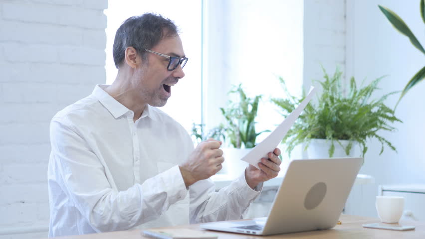 Man Reading Contract and Gets Excited for Success | Shutterstock HD Video #1009437767