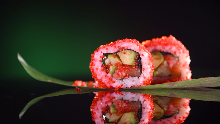 Sushi roll rotated on black background. Sushi japanese food in restaurant. California Sushi roll set with salmon, vegetables, flying fish roe and caviar closeup. Japan restaurant menu. 4K UHD video