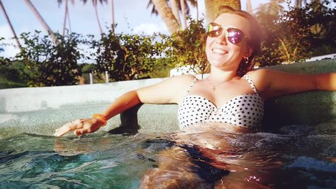 Young happy woman in sunglasses relaxed in hot tub Enjoying her life in swimming pool outdoors during sunset. Spa treatments. slow motion. 1920x1080
