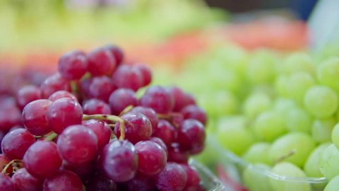Dynamic close up of red grapes on a local farmers market with moving camera in warm colors in soft-focus in the background