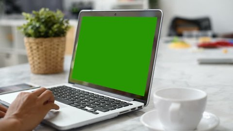 Woman hand using laptop with key green screen. Lady hand typing on a laptop computer.