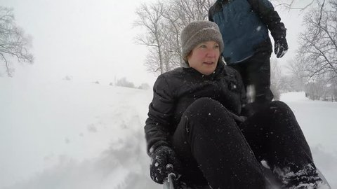 Mature woman on sled outdoor on snowy winter afternoon.