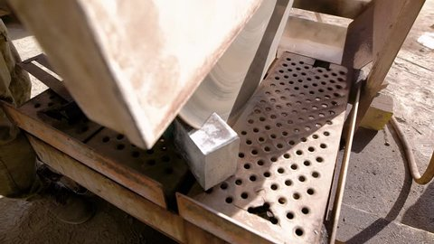 A close shot at the stone cutting machine, an industrial sharp blade divides into two halves of the mineral, which is on the construction