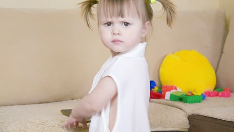 toddler girl turns around. serious look to camera. angry, sad child. pretty adorable  baby incomprehensible, perplexed. expression emotion of anger, sadness, worried. Portrait of female, caucasian kid