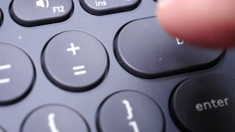 Closeup of finger pressing backspace button on the black computer keyboard. Technology. Slow motion