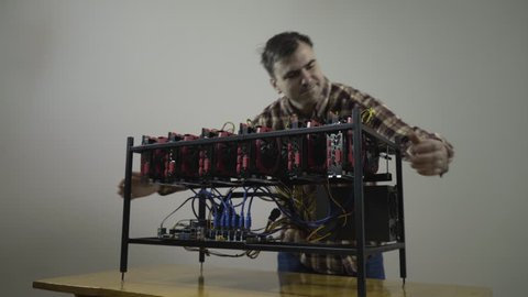 Be rich to do nothing! All happy capable young smiling man hugging and caressing his gpu btc bitcoin mining rig machine with powerful graphics cards, concept cryptocurrency computer, symbolic shot.