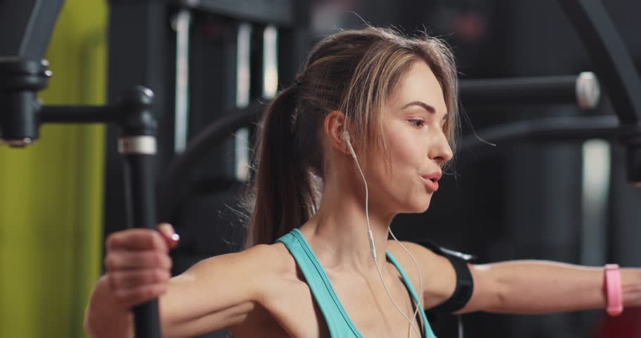 Young woman listening to music in headphones engaged in a gym  | Shutterstock HD Video #1009507607