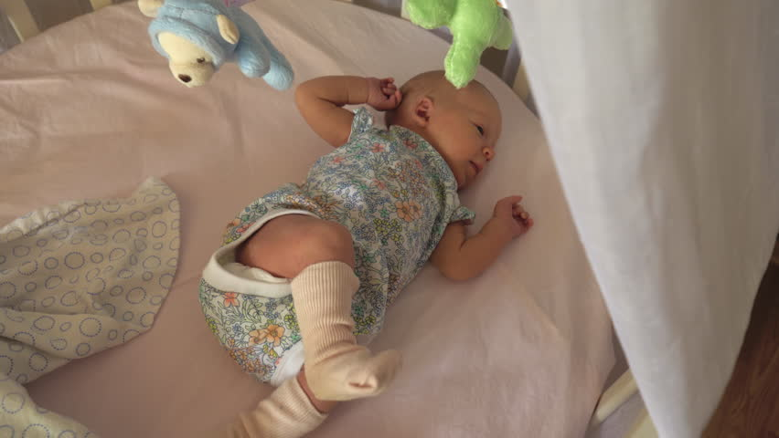 Baby girl lying in crib and having a hiccup. Musical toy mobile spinning overhead