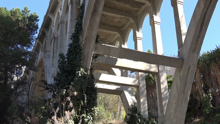 Tilt shot of the underside of a concrete arch bridge, the Historic Shakespeare Bridge in Los Angeles