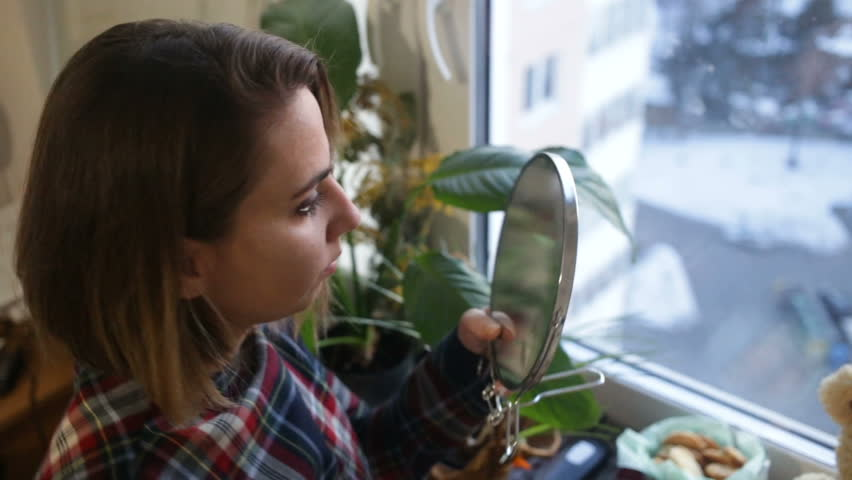 The girl looks to smear a mirror with fingermarks. Top-down view, closeup, sunset, natural light, indoors, real time | Shutterstock HD Video #1009516547