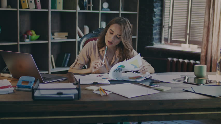 Attractive business woman reading documents at desk. Study of growth charts. Business process work in home office. Working woman analysing data. Market research concept. Marketer analyse market data